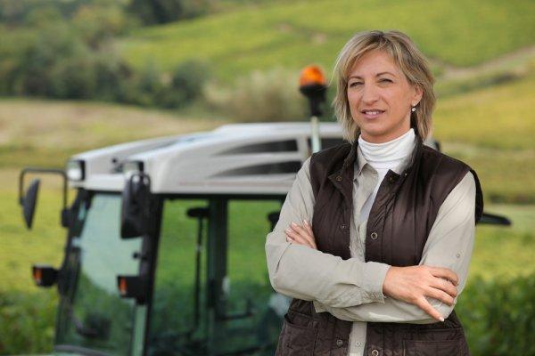 Female farmer, in front of tractor, in a field.