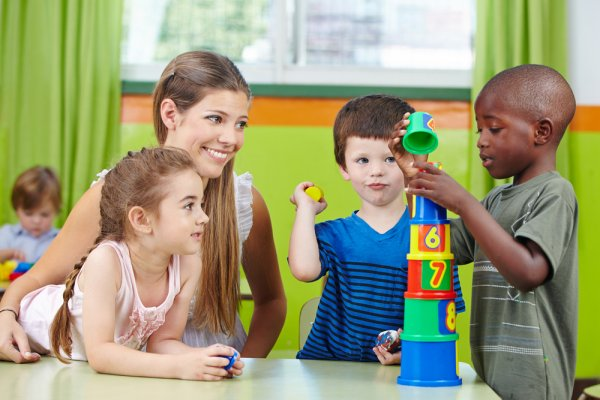 Child care worker with children in classroom.