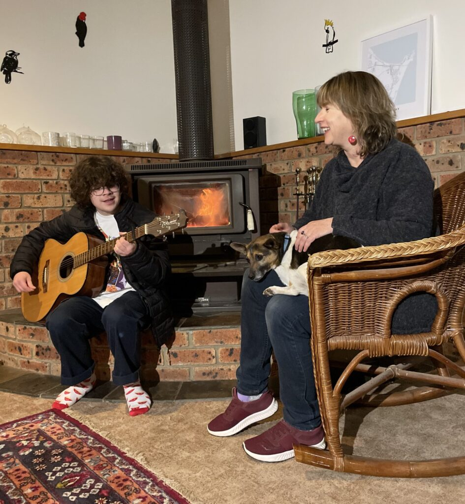 Nick playing guitar with Rachel by the fire. Picture: Supplied